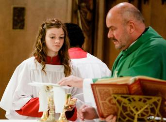 A female altar server assists at a Mass celebrated by Cardinal O'Malley in 2013.Pilot file photo/ Gregory L. Tracy